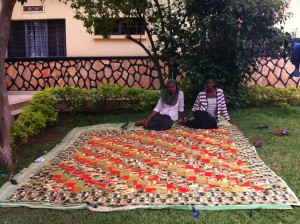 Two members of the Tubahumurize Co-Op laying out a quilt